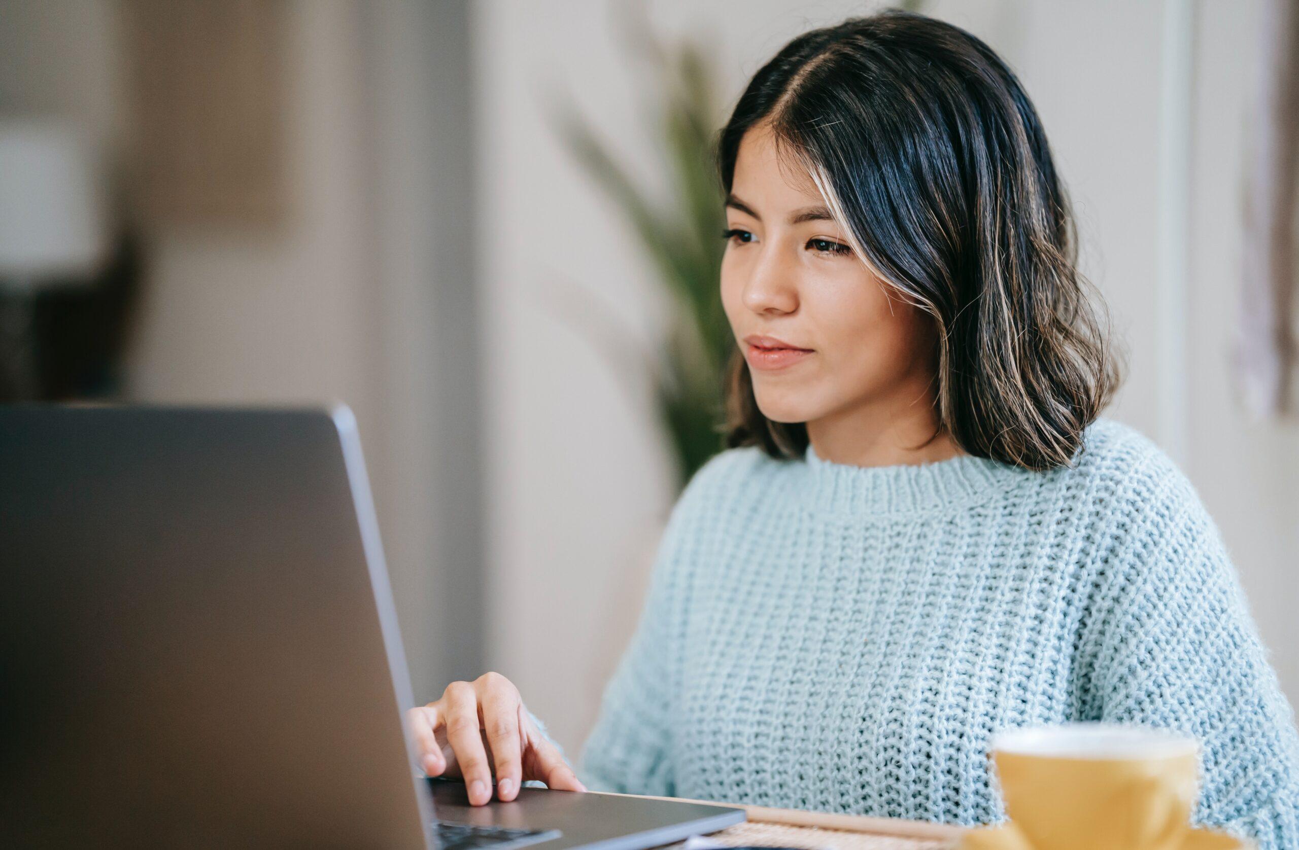 Hispanic woman working on laptop